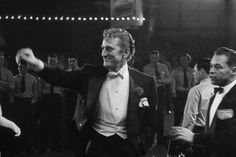 Kirk Douglas, elegant in white tie, smiles and waves as he enters the RKO Pantages Theatre in 1954.