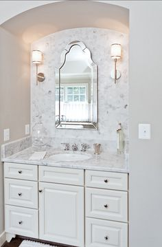 Marble backsplash, mirror, sconces and painted cabinet #Bathroom
