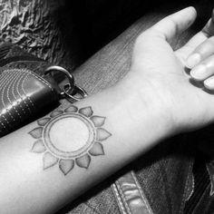 Little forearm tattoo of the sun on Mira Subramanian.