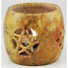 """Carved of soapstone, this votive holder is an elegant piece perfect for any altar or home. It measures approximately 2 3/4"""" in diameter, easily accommodating any votive candle, and has been carved with decorative cut outs to allow the light of your candle to spill out and provide ventilation. These cut outs have taken the form of pentagrams on opposing sides, spaced evenly with decorative designs cut into the stone between them. This votive holder measures approximately 2 3/4"""" tall."""