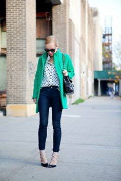 green coat with polka dots top and jeans