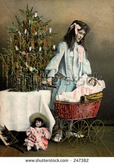 Little girl playing with her Christmas dolls and carriage