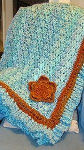 This Turquoise and Orange Afghan is so beautiful with its flower embellishment. Soft and fluffy yarn is used with single crochet and double crochet in this free crochet afghan pattern. Make it today so you can wrap yourself up in it.
