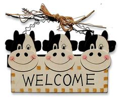 """Welcome Plaque !  Makes moo feel right at home !  CowDorable inexpensive wooden welcome plaque hangs indoors or outdoors. Very lightweight so it hangs on just about any tack, screw or finishing nail.    The raffia 'hay' is a nice touch. It's cute !    NU500 Size 12"""" wide Price 7.95  http://www.cowdepot.com/cowdecor.html"""