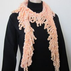 This beautiful scarf is very skinny and long and has a lot of fringes on both sides It is hand knitted with polyester imported yarn in silky peach color It