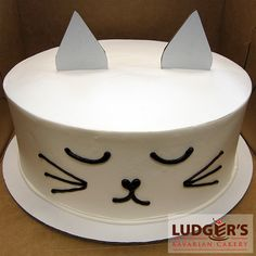 Kitty cat cake! Bavarian cream cheesecake with whipped vanilla frosting with cardboard ears and chocolate icing kitten face drawing