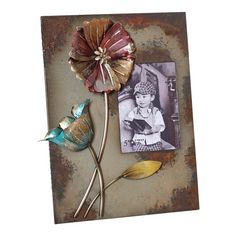 Warmly weathered picture frame with floral detail.     Product: Photo frameConstruction Material: Metal and glass...