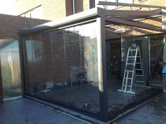 Montage van een overkapping met glaswanden, compleet glazen tuinkamer uitgevoerd met serre zonwering. Uiteraard maken wij ook de werkplek volledig schoon na montage