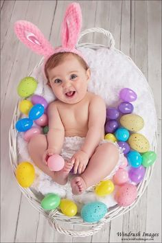 Baby girl photographed in Calgary photo studio in a basket surrounded by eggs wearing bunny ears