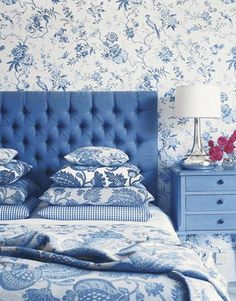 A symphony of blue toile fabrics is broken up only by a solid blue headboard and night stand. A sleek silver lamp and bright pink flowers add a hint of contrast.