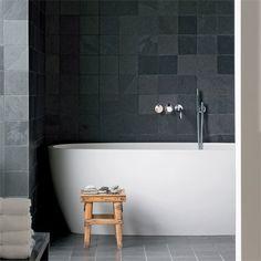 La salle de bains avec baignoire en Corian sol en pierre grise et mur carrelé de noir
