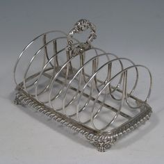 Antique Georgian Scottish sterling silver Regency style seven-bar toastrack with cast shell handle, lions-paw feet, and gadroon edge. Made by George Bell of Edinburgh in 1822. Length 17.5 cms (7 inches), height 13 cms (5 inches), width 11 cms (4.25 inches). Weight approx. 10 troy ounces (310g).