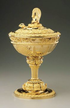 A solid gold military cup designed in Russian neoclassic style, presented in1833 to General-Adjutant Count Stepan Fedorovich Apraksin, who took part in the Russian war against Napoleon in 1812 and went on to a have distinguished military career.  The handle of the cup's lid is finely carved to resemble the plumed helmet of the Imperial House Guards.