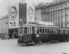 """A streetcar decorated with swastikas passes billboards displaying Hitler's face. The billboards urge Austrians to vote """"Ja"""" (Yes) in the upcoming plebiscite on the German annexation of Austria. Vienna, Austria, April 1938."""