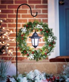 Hang a Christmas wreath and a solar lantern on a shepherd's hook in the front yard