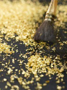 FEUILLES D'OR - Afin d'habiller votre table de manière originale, appliquez de l'or en poudre à l'aide d'un pinceau sur votre nappe. Cette dernière peut être blanche ou encore marron foncé pour un meilleur effet.