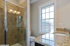 Modern Bathroom with Natural Light and Glass Shower Door Granite Countertop on Church Street courtesy of Kinzie Real Estate Group #interiordesign #kinziegroup #modern #realestate #dreamhome #architecture