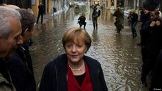 German Chancellor Angela Merkel (C) inspects a flooded street near the Elbe river in the east German town of Pirna June 4, 2013. Pictured at left is Saxony State Premier Stanislaw Tillich. REUTERS/Thomas Peter (GERMANY - Tags: POLITICS DISASTER ENVIRONMENT)