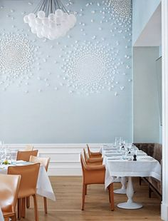 Pale blue walls form a sophisticated backdrop with clustered cloud-like lights and a ceramic blossom installation by Brazilian artist Valeria Nascimento at London's Spring Restaurant. Interior design by Briony Fitzgerald. Lights by Apparatus.
