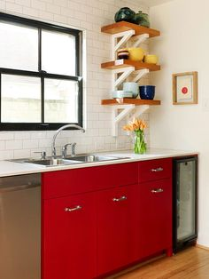 Bring color and interest into your kitchen with scarlet cabinetry. The bold red hue on these cabinets adds interest to this otherwise neutral kitchen. Open shelving used above the countertop ensures that the striking cabinet color doesn't overwhelm the small space.