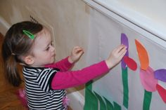 creating a flower using construction paper on a Spring mural