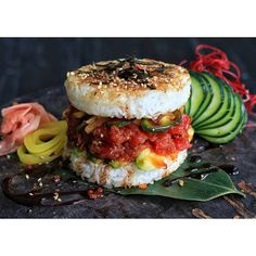 """This burger features spicy tuna, avocado, cucumbers, and oshinko between grilled rice """"buns"""" topped with seaweed. Sushi Burger, Burger Buns, Burger Food, Spicy Tuna Recipe, Tuna Rice, Food Porn, Tasty, Yummy Food, Food Trends"""