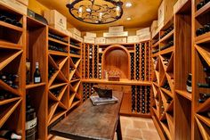 Traditional Wine Cellar with limestone tile floors, Chandelier, Built-in bookshelf