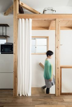 Curtains replace walls inside this renovated townhouse in Japan.
