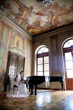 Bride and groom playing piano inside old manor in Dolna Krupá Slovakia by zdenkaimekov