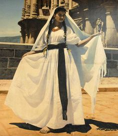Oaxaca Woman Mexico Another in a series of old photos displayed in the Oaxaca Mexico post office. This model wears a white huipil, long white skirt, and a white rebozo covering her head and shoulders.