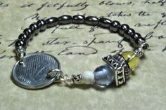 50 Centavos Brazilian coin bracelet with glass, howlite and silver color beads.  Round and oval hematite beads are on stretch cord.