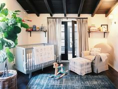 Estee Stanley - Chic nursery design with wood beams, shelves flanking black French doors covered in light beige curtains, Oeuf Sparrow Crib Gray, peacock blue rug, ivory glider & ottoman and fiddle leaf fig plant.