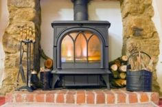 A pretty look for the wood burning stove. Stone accent on the outside with room to store wood between.