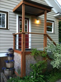 Cheap, easy porch railing and roof. Treated lumber, corrugated tin roof, galvanized conduit for mid-rails. Except stairs in front. Front Porch Railings, Porch Awning, Patio Railing, Porch Stairs, Porch Roof, Side Porch, Pergola Patio, Deck Awnings, Wisteria Pergola