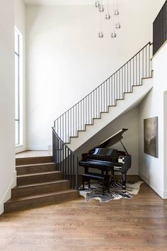 Stunning entryway with wood floors, a floating staircase and a piano