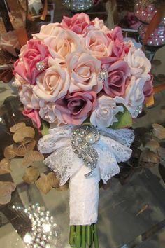 Lindo bouquet em rosas em e.v.a. bouquet contém 43 rosas e folhagem verde, nas cores rosa & pink com ornamentações em STRASS e pérolas sintéticas, bouquet revestido de renda e laço de renda, e para finalizar um lindo broche  Pontos de luzes em pérolas e um belo broche em STRASS com pérolas fecham esta bela jóia!  As rosas em e.v.a.possui textura,aparência e toque de uma rosa natural.  Bouquet disponível nas seguintes cores: vermelho - lilás - rosa - roxo - laranja - branco puro - champagne…