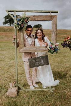 Groom in pink suit, bride in ASOS wedding dress, posing in outdoor DIY wedding photobooth with wooden picture frame on a stand. Diy Wedding Photo Booth, Rustic Wedding Photos, Wedding Picture Frames, Diy Photo Booth, Wedding Props, Wedding Frames, Wedding Blog, Picture Booth, Photos Booth