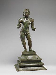 """Pieza que data del siglo XI, en el periodo Chola(880–1279). El popular santo niño del siglo VII. """" Es uno de los muvar, los tres principales santos de la India del sur. La leyenda cuenta que después de recibir un regalo de la leche (representado por la taza) de la diosa Uma, la Sambandar infantil dedicado su vida a componer himnos en alabanza del Señor Shiva, sus elevados puntos de la mano a la morada celestial de Shiva en el Monte Kailash, en el Himalaya."""""""