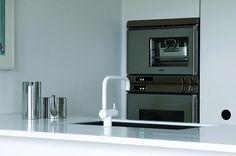 I Rikke og Martins køkken er der blevet plads til både en al-mindelig ovn og en dampovn, begge i rustfrit stål ligesom den aflange vask. Bordet er hvid corian. Armatur med med 360-graders dobbelt svingbar tud med vandbesparende luftindblander, 5.805 kr., Vola.