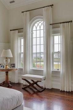 Las cortinas que se utilizaron para trabajar en esta habitación se usan para llamar atención a la arquitectura de las ventanas.