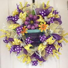 """Purple & Yellow Polka Dot Wreath"" ($95) This cheerful, brilliant spring wreath is an eye catcher for your front door. It is 26""x26""x7"" deep, on a white wire frame, vivid purple deco mesh, yellow & white poly deco mesh ruffles, iridescent white flex tubing bows, metal flower pot embellishment, yellow glitter curl picks, and 2.5"" yellow and purple polka dot ribbon. If you or anyone you know is interested, please message me for details. Thank you!"