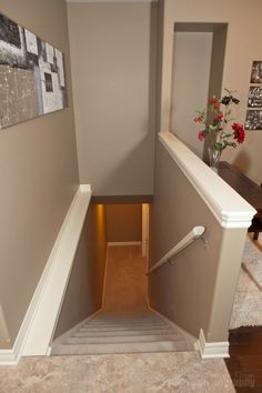 Building a half wall for an open staircase railing makes the stairs unnoticeable from the living room, without making the room feel smaller.