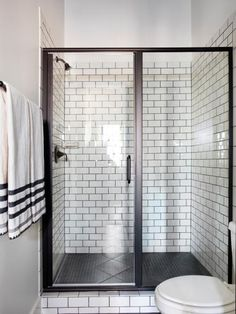 Walls of clear glass in a semi-frameless shower enclosure allow views of white subway tiles with contrasting grout that line the shower and create a sharp look.