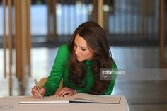 Catherine, Duchess of Cambridge signs the visitors book after touring the National Portrait Gallery on April 24, 2014 in Canberra, Australia. The Duke and Duchess of Cambridge are on a three-week tour of Australia and New Zealand, the first official trip overseas with their son, Prince George of Cambridge.  (Photo by Lukas Coch - Pool/Getty Images)
