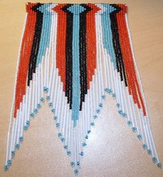 This bead work has the colors of black, white, red, and turquoise. The red and turquoise represent the colors of the Cherokee nation that Taylor is related to. Her 'Damn I'm Good' T-shirt has these colors.