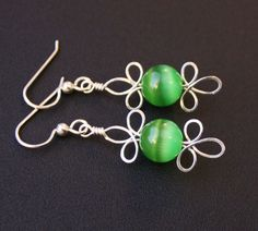 These enchanting earrings are handcrafted with .925 sterling silver and a beautiful vibrant green glass cats eye stone. Design is Irish and Elven inspired, with the elegant yet fun triple leaf motif evoking a Celtic knot or clover. Earrings dangle comfortable sterling french hooks, and ship nicely gift boxed as shown in last photo. Exact measurements shown in 2nd to last photo.  Interested in a different stone color? Contact me! I can make this same design with a variety of stones or beads.