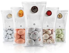 Wonderfully minimal packaging allows the beauty of Hatziyiannakis pebbles - round candy with a core of juicy fruit or nuts and bitter chocolate covered with a thin sugar coating - to shine. The interior view (haha) is helpful and enticing. Designed by Mousegraphics.