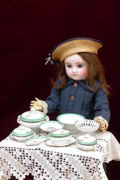 Exquisite Steiner Series C/6 bébé standing in front a French miniature porcelain set, Paris 1880s.