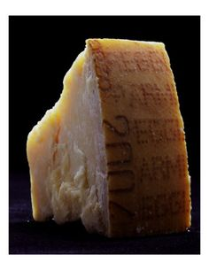 Gourmet - January 2007. The fine layers in this wedge of Parmigiano-Reggiano cheese are illuminated here as if by a shaft of sunlight; the rind is stamped with the official logo of the Consorzio di Parma. This Romulo Yanes food photograph is an outtake from a January 2007 Gourmet magazine feature.