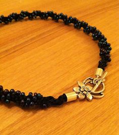Spiral kumihimo necklace using black rattail and various dark coloured seed beads